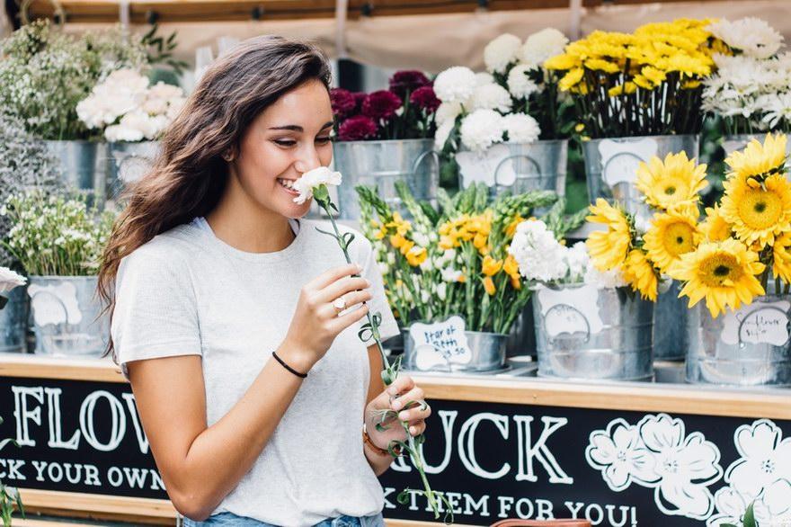 Uśmiechnięta kobieta z kwiatkiem.